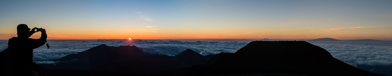 Panorama of the sunrise view from the summit of Haleakala. The two volcanoes on the horizon to the right are Mauna Kea and Mauna Loa on the Big Island. Silhouette of random tourist with point&shoot camera on the left.